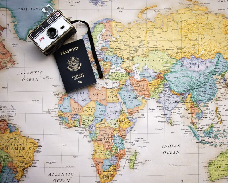organising holiday with a map, passport and camera